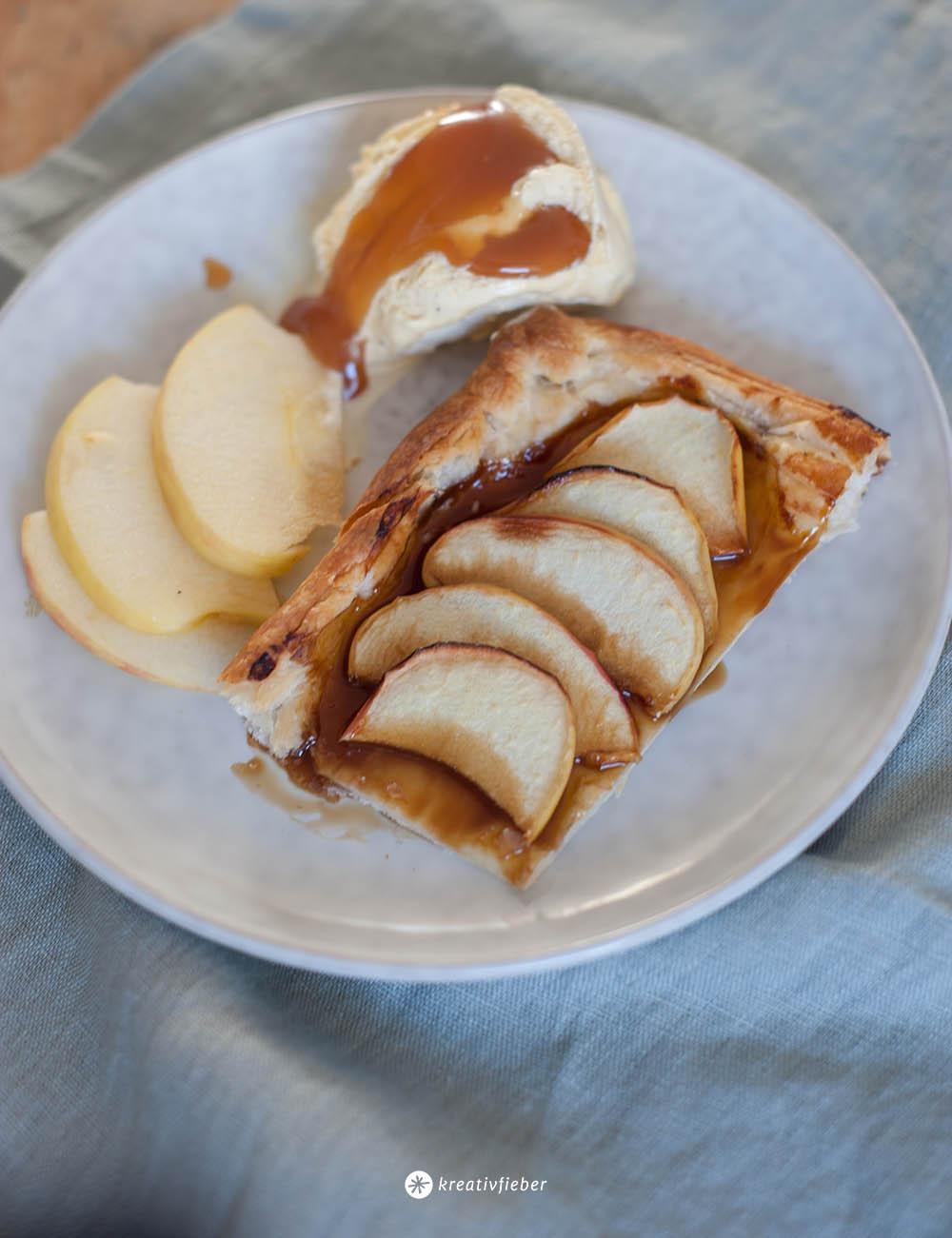 Apfelkuchen auf Blätterteig mit Vanilleeis und Karamellsoße auf einem Teller