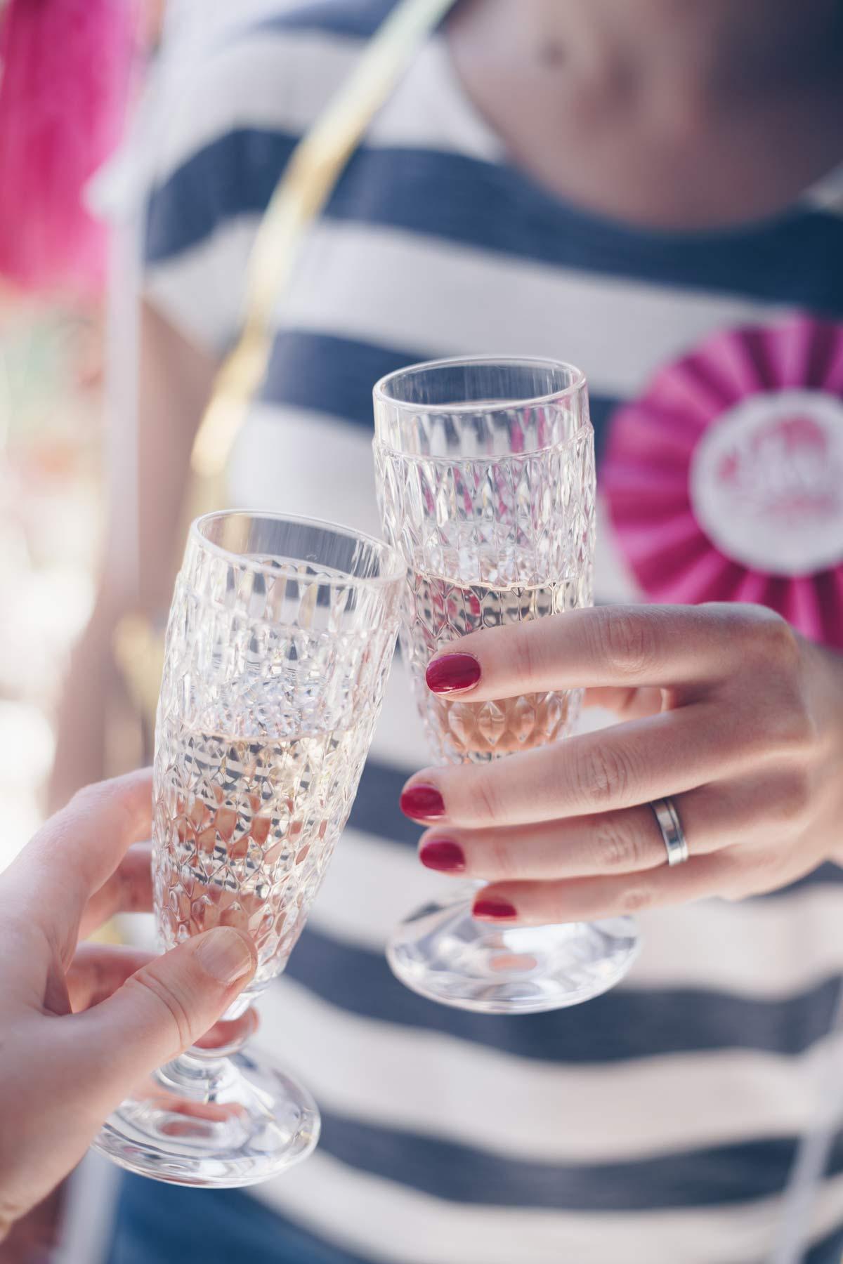 Tipps für den perfekten JGA - die Braut stößt mit der Trauzeugin mit zwei Sektgläsern an