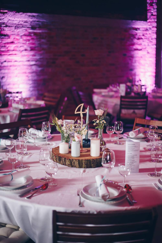 Hochzeitsdeko Inspiration für eine Scheunenhochzeit - lockere Blumen, Baumscheiben und blau grüne Vasen